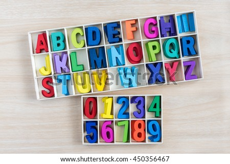colorful alphabet letters and number in a wooden box with square compartments for teaching kids to read and spell, overhead view - stock photo