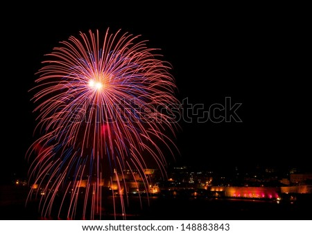Colorful amazing fireworks with city silhouette in Malta, Valletta, dark sky background and house light on the bottom, Malta fireworks festival, 4 of July, Independence day, festival - stock photo
