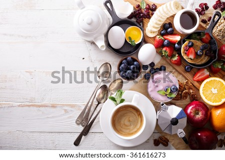 Colorful and tasty breakfast ingredients on white table - stock photo