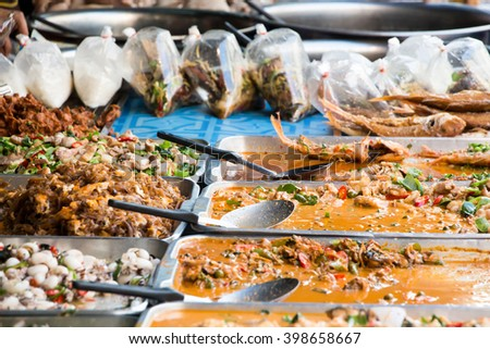 Colorful and tasty curries in trays at a grocery shop in Thailand - stock photo