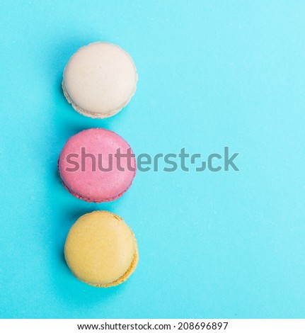 Colorful and tasty  French Macarons on blue background.Top view. - stock photo
