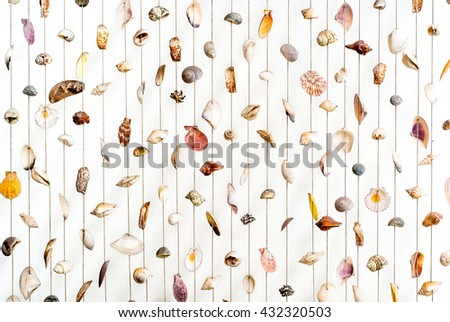 Colorful and Variety seashells hanging on the white isolated wall - stock photo