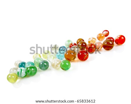 Colorful antique marbles on a white reflective surface - stock photo