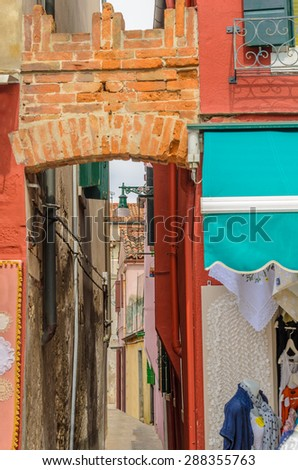 Colorful apartment buildings at very narrow street in Burano, Venice, Italy. - stock photo
