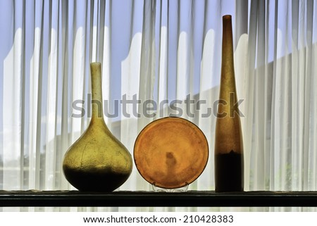 Colorful architectural bottle and plate display shot against white, translucent curtain - stock photo