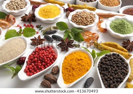 Colorful, aromatic Indian spices and herbs on a wooden white  background. - stock photo