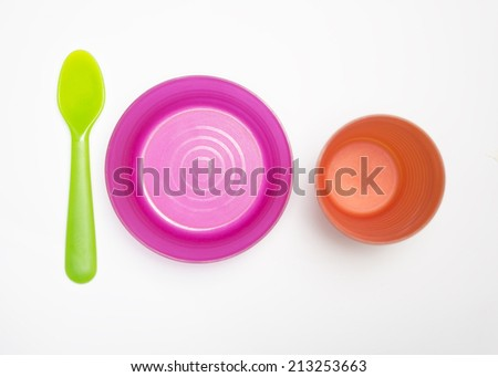 Colorful arrangement of plastic spoon, bowl and cup for kid isolated on white - stock photo