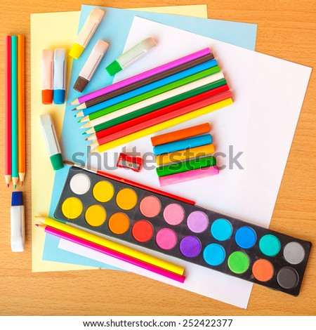 Colorful art supplies on a school desk - stock photo