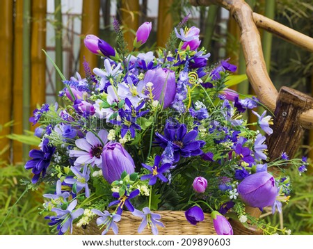colorful artificial flowers on basket - stock photo
