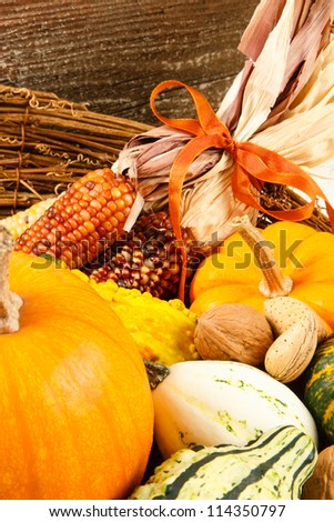 Colorful autumn harvest vegetables make a colorful Fall decoration sitting in a basket against a wood background - stock photo