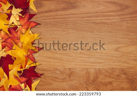 Colorful autumn leaves lay on a wooden background - stock photo