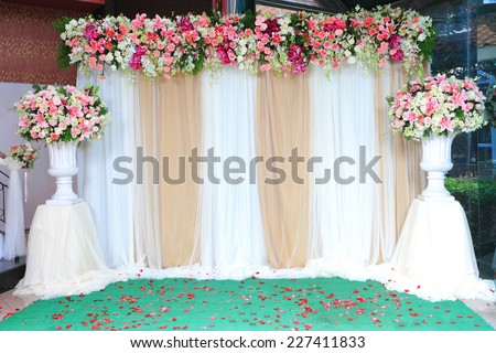 Colorful backdrop flowers with white and gold fabric arrangement ready for wedding ceremony. - stock photo