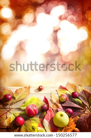 Colorful background of fallen autumn leaves and appeles on wooden table with sunbims/ Thanksgiving day concept/ - stock photo