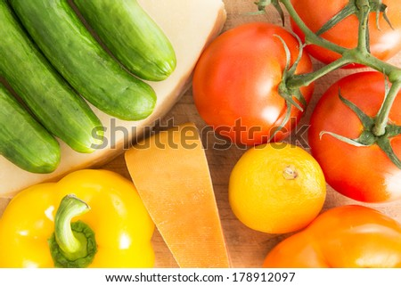 Colorful background of healthy fresh groceries with a close up overhead view of baby green cucumbers, yellow sweet pepper, ripe red grape tomatoes, a lemon and wedge of cheese with an orange rind - stock photo