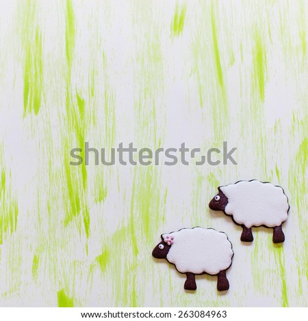 Colorful background with two little sheep cookies decorated with royal icing. - stock photo