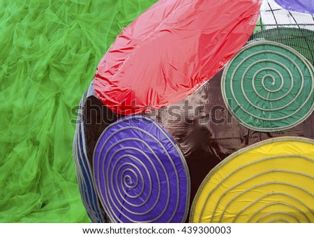 Colorful ball decoration. A close-up shot. The ball was made of colorful, glossy plastic fabric and steel wire. There are red, green, purple, yellow and blue colors in the image.  - stock photo