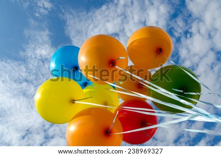 colorful balloons flying in the clouds - stock photo