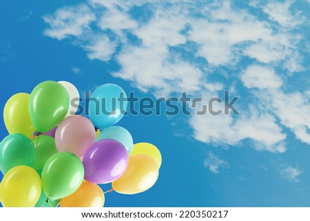 Colorful balloons on blue sky - stock photo