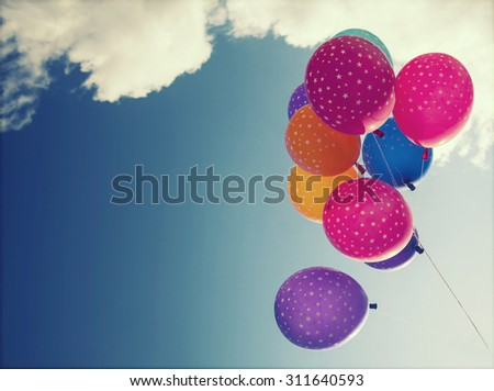 Colorful balloons on blue sky. Concept of love in summer, valentine, wedding and honeymoon. Retro styled photo - stock photo