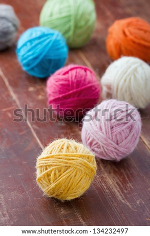 Colorful balls of woolen yarn on old vintage red wooden background - stock photo