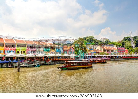 Colorful bars and restaurants dot the Singapore River along Clarke Quay. Once a warehouse, the area is now converted into a popular meeting place for locals and tourists alike. HDR rendering. - stock photo