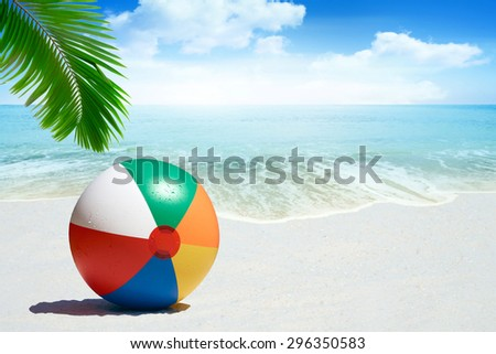 Colorful Beach ball on sandy beach with palm frond - stock photo