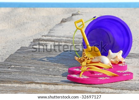 Colorful beach supplies and shells on boardwalk - stock photo