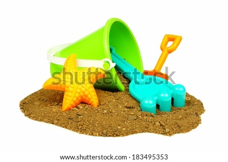 Colorful beach toys in a pile of sand over a white background - stock photo
