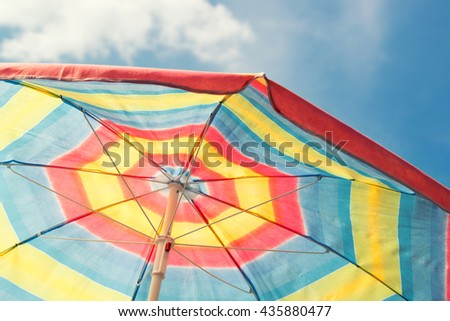 Colorful beach umbrella against blue sky, vintage filter - stock photo