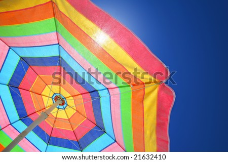 Colorful beach umbrella against sunny blue sky - stock photo