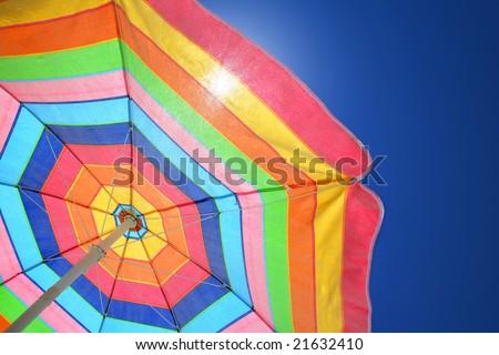 Colorful beach umbrella against sunny blue sky - stock photo