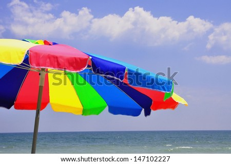 Colorful beach umbrella at the beach  - stock photo