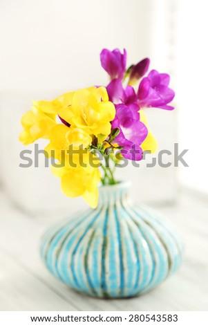 Colorful beautiful freesias on wooden windowsill - stock photo