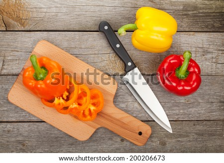 Colorful bell peppers and kitchen utensils over wooden table background - stock photo
