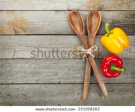 Colorful bell peppers and kitchen utensils over wooden table background with copy space - stock photo