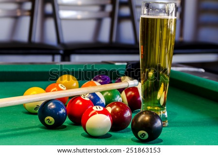 Colorful billiard balls and pool stick sitting on pool table with glass of beer - stock photo