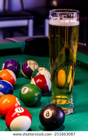 Colorful billiard balls sitting on pool table with glass of beer - stock photo