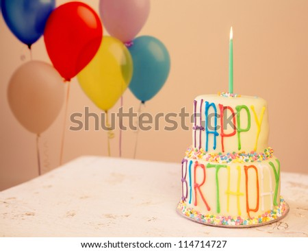 Colorful birthday cake with candle - stock photo