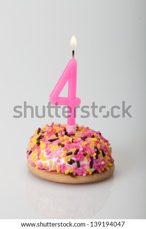 colorful birthday cake with candle for four - stock photo