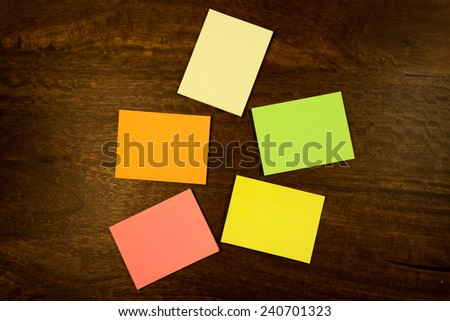 Colorful blank sticky notes lying on a  dark mahogany table. View from the top. - stock photo