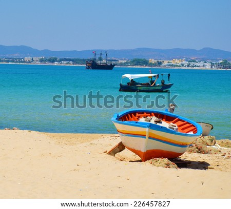 Colorful boat laying on the beach with Tunisian sea in the background - stock photo