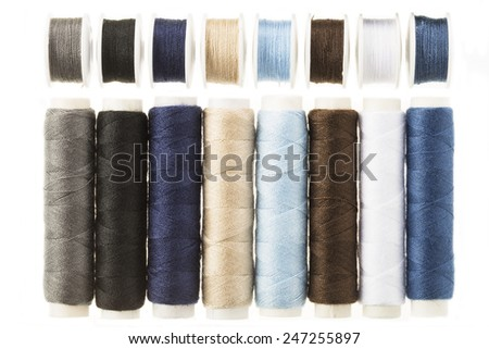 Colorful bobbins and spools of threads isolated on white - stock photo