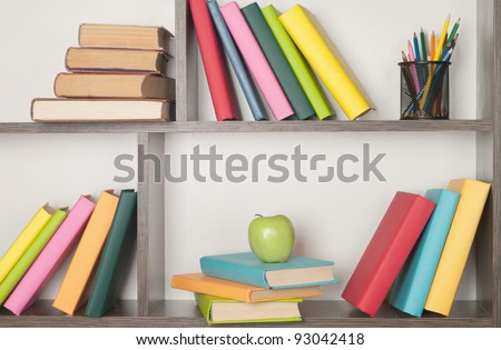 colorful book, apple and pencils on the bookshelf - stock photo