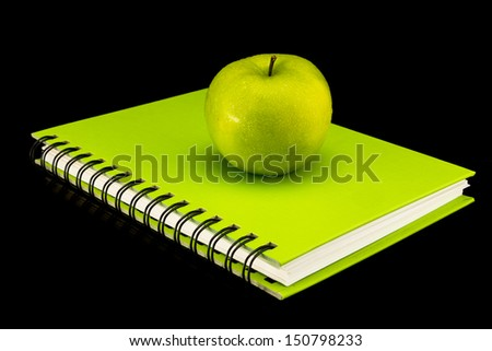 Colorful book with green apple - stock photo