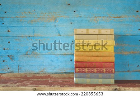 colorful books on a wooden shelf, free copy space  - stock photo