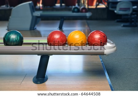 Colorful bowling balls ready to start - stock photo