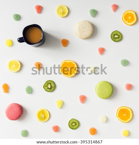 Colorful bright fruit pattern with coffee mug and sweets on white background. Flat lay. - stock photo