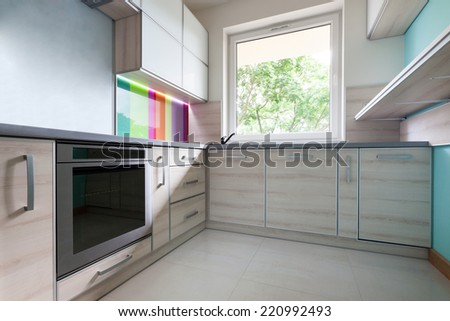Colorful, bright, modern kitchen with big window - stock photo