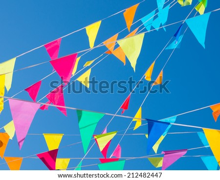 colorful bunting flags against a blue sky - stock photo