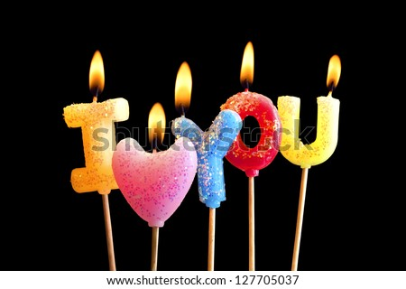 Colorful burning candles making 'I love you' isolated on black (clipping path included) - stock photo